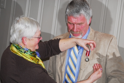 Peter Lambrick's wife, Liz, gets the honour of pinning his Queen's Jubilee Medal on him.